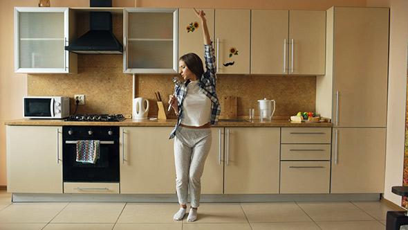 Femme qui chante dans sa cuisine