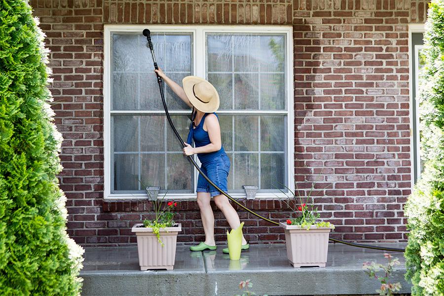 femme qui nettoie une vitre dehors