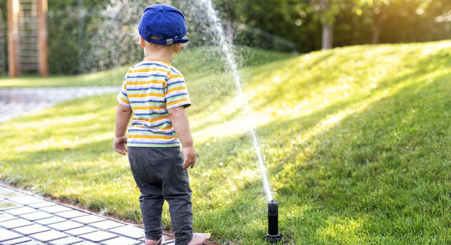 Enfant jouant avec l'arrosage automatique